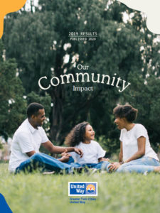 2020 Our Community Impact. Image of parents and their daughter sitting in a park.
