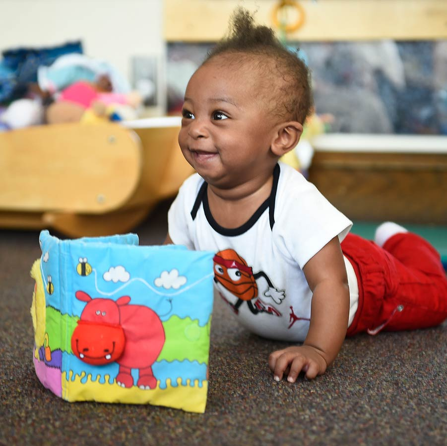 Early Childhood - Baby, in tummy, looking at a book