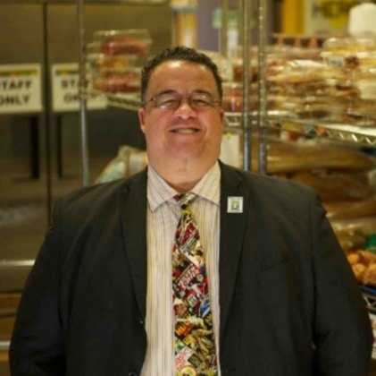 Jonathan, Executiove Director at Hallie Q. Brown stands in front of shelves of food